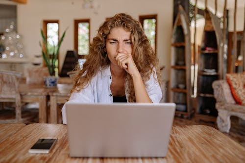 Photo of Woman Looking Serious While Using Laptop