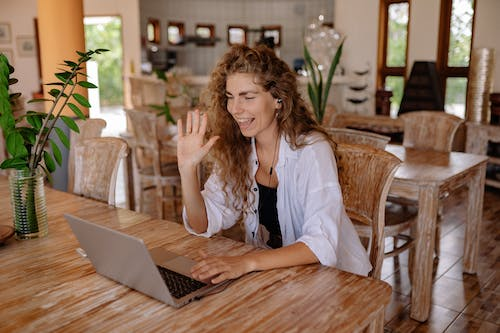 Woman in White Shirt Sitting on Chair in Front of Macbook