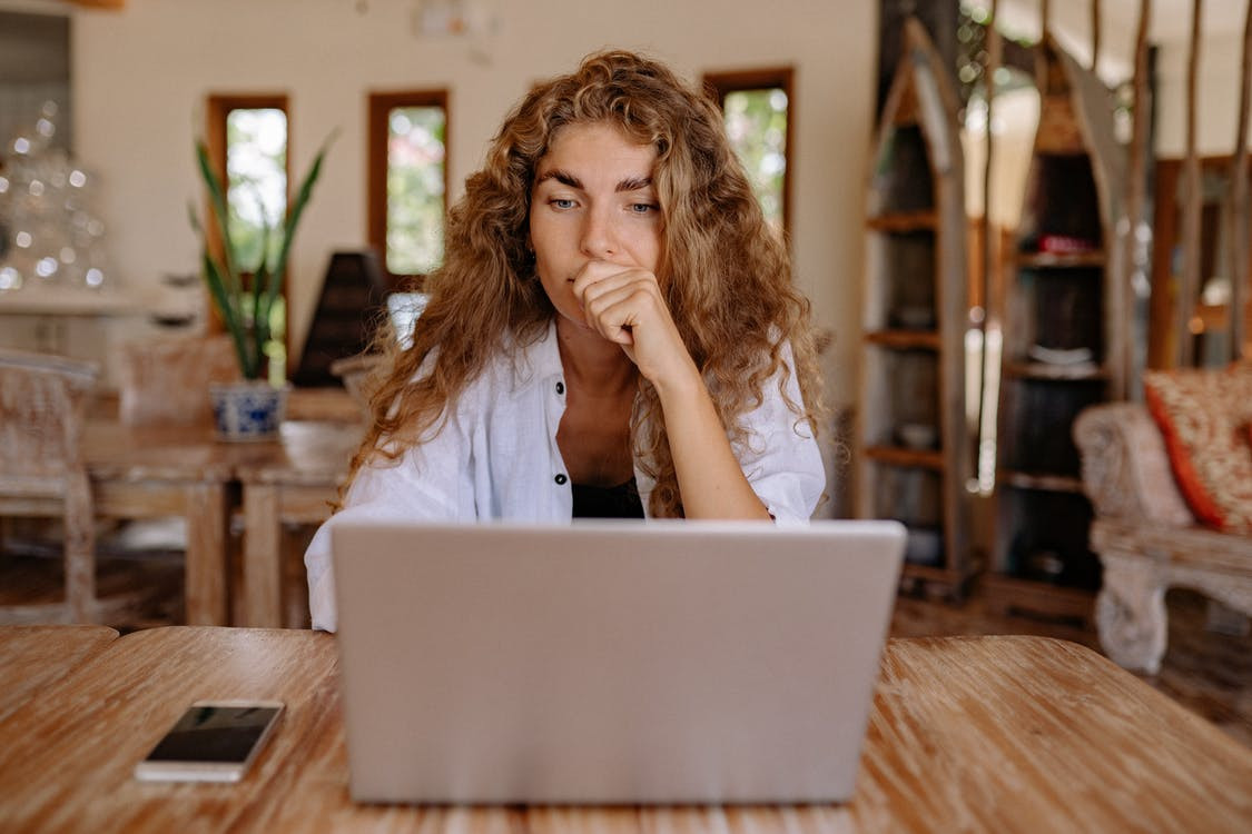 Woman in White Button Up Shirt While Using Laptop