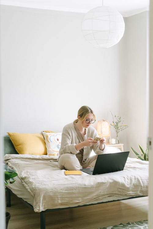 Photo of Woman Sitting on Bed While Using Smartphone