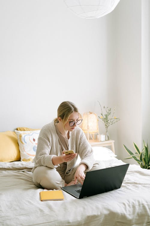 Photo of Woman Sitting on Bed While Using Black Laptop