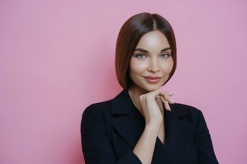 Positive woman near pink wall