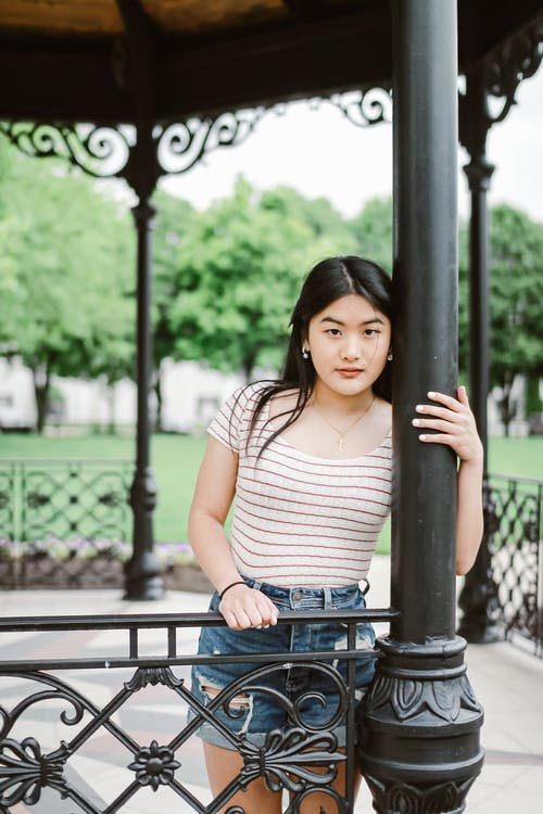 Young Asian woman standing near railing in park