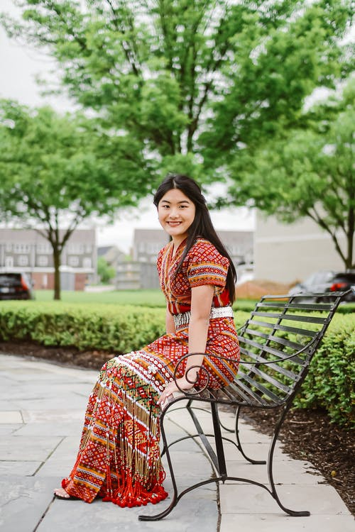 Positive Asian woman sitting on bench
