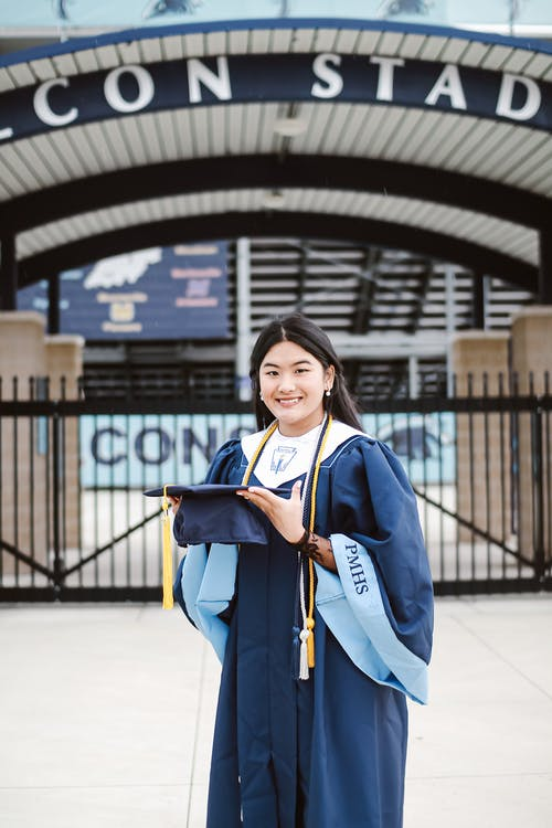 Smiling Asian female wearing dark blue academic robe and holding academic square cap while standing outside university campus on sunny day