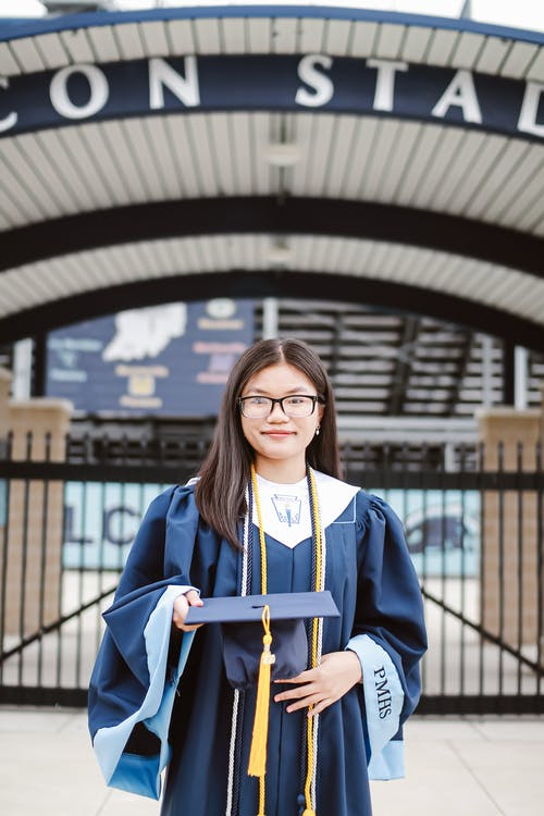 Content young Asian lady wearing blue academic robe and holding square cap while standing outside college campus