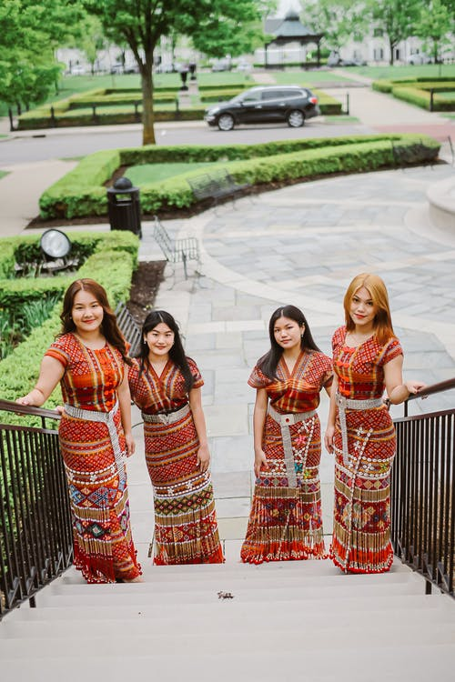Charming Asian women in traditional clothes in park