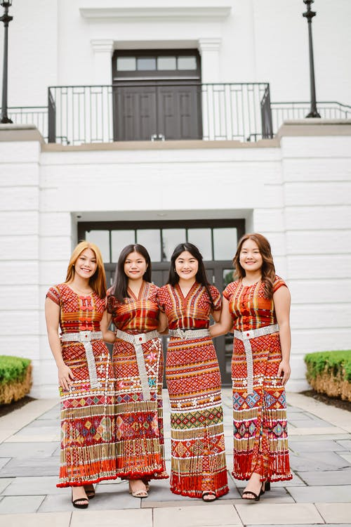 Cheerful Asian women in authentic dresses outside modern building
