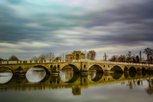 Old arched bridge over peaceful river on overcast day