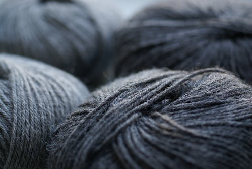 Skeins of gray woolen yarn on table