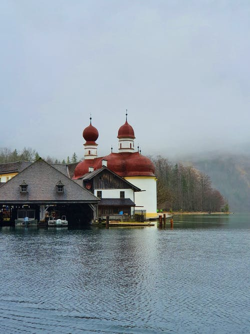 Aged Catholic St. Bartholomew Church with brown tiled cupolas located on calm pond shore on foggy day in Germany