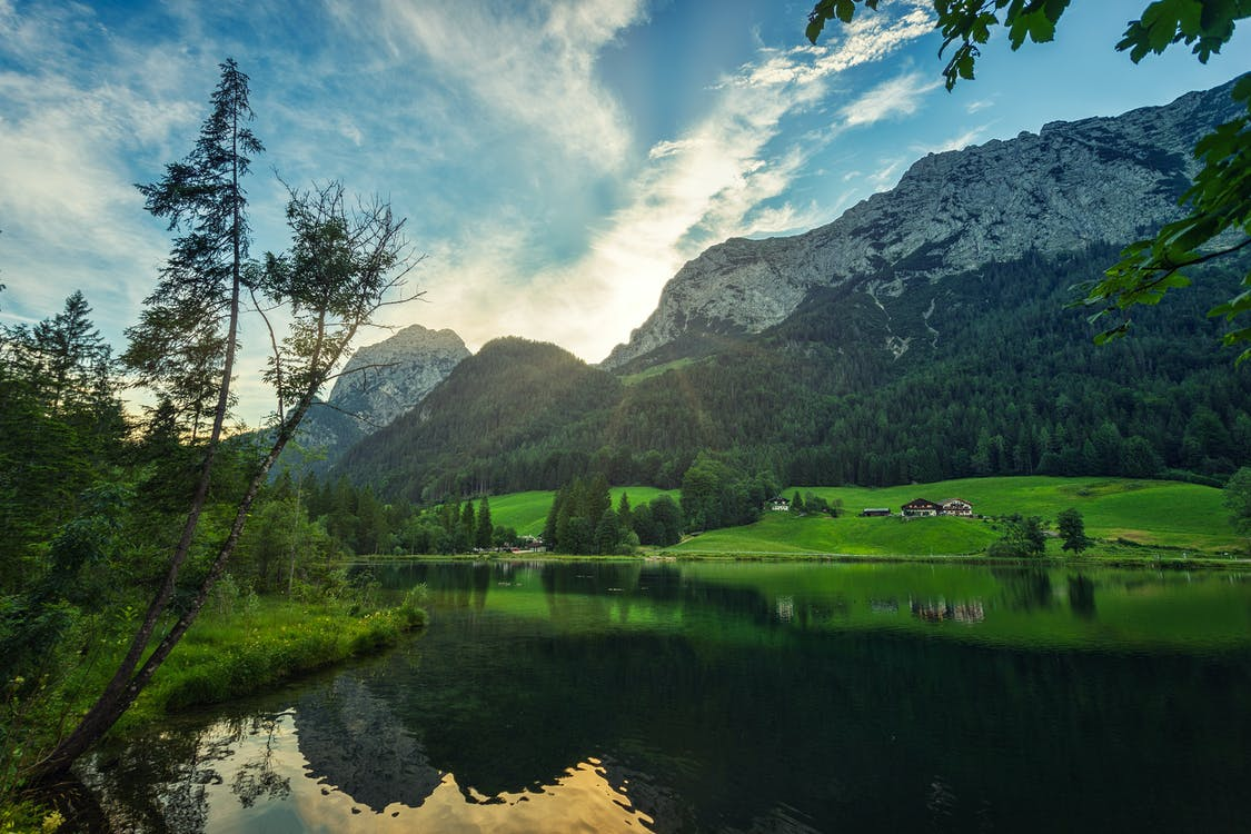 Breathtaking view of calm pond and lush green valley located on severe rocky mountain bottom on clear summer day