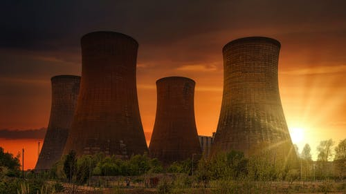 Exterior of huge cooling towers located in contemporary atomic power plant against bright setting sun under dramatic dark sky