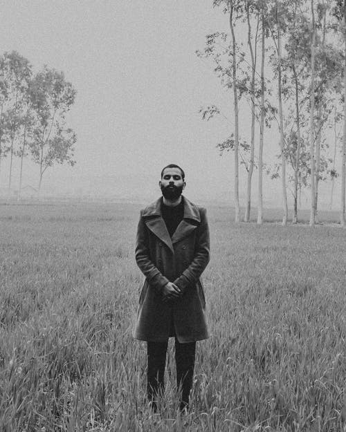 Black and white contemplative ethnic male in stylish coat standing with hands folded and eyes closed foggy nature