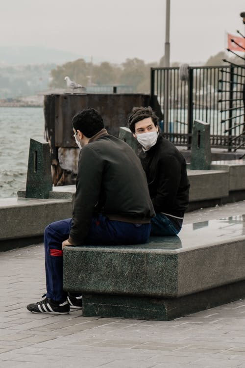 Men in face masks sitting on waterfront in cold weather