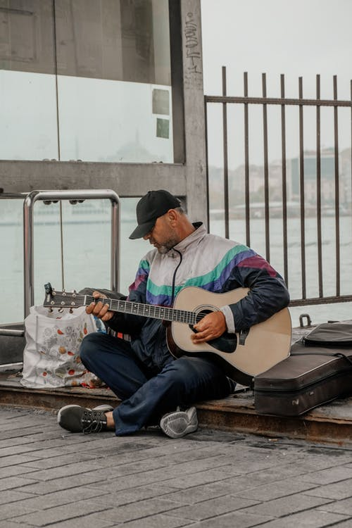 Street musician playing guitar on sidewalk