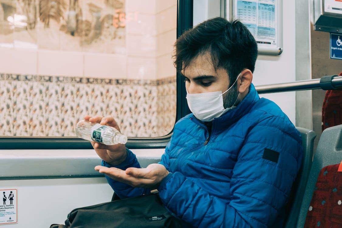 Man in mask applying hand sanitizer during bus trip