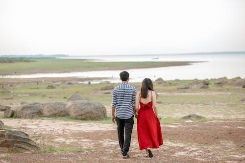 Romantic couple walking on sandy riverside
