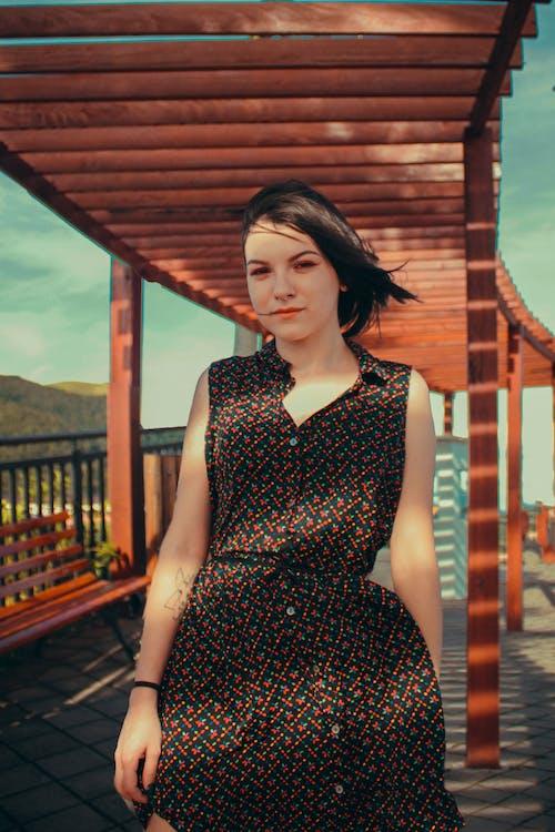 Woman in Black and White Polka Dot Sleeveless Dress Standing on Wooden Bridge