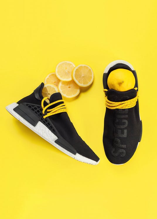 Top view of pair of trendy black trainers with white outsole placed on yellow surface with fresh natural lemons