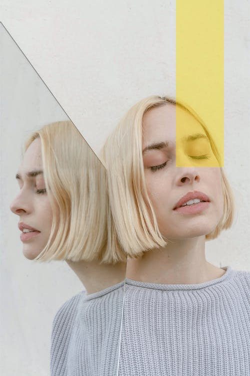 Pensive young woman with closed eyes reflecting in mirror