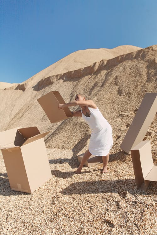 Informal young woman carrying carton boxes in desert on sunny day
