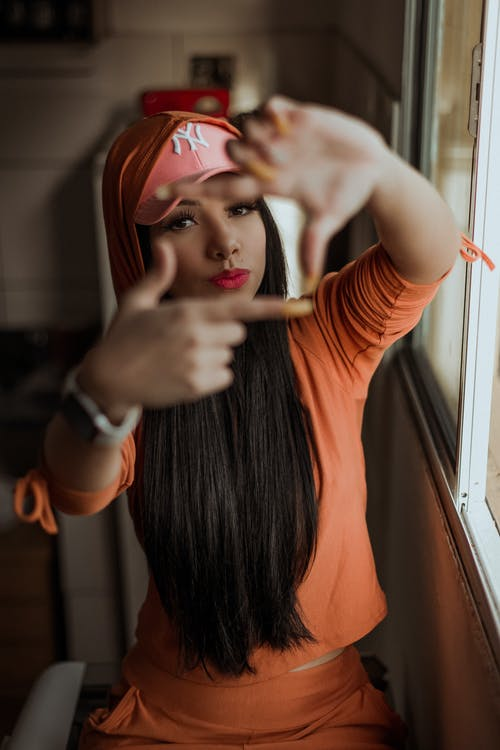 Confident young ethnic female with long dark hair in stylish sportswear and cap making frame gesture with fingers and looking at camera