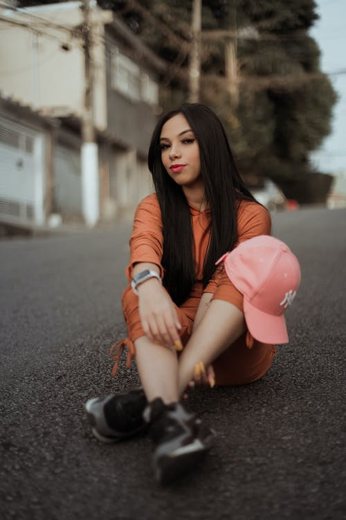 Woman in Brown Leather Jacket and Orange Skirt Sitting on Road