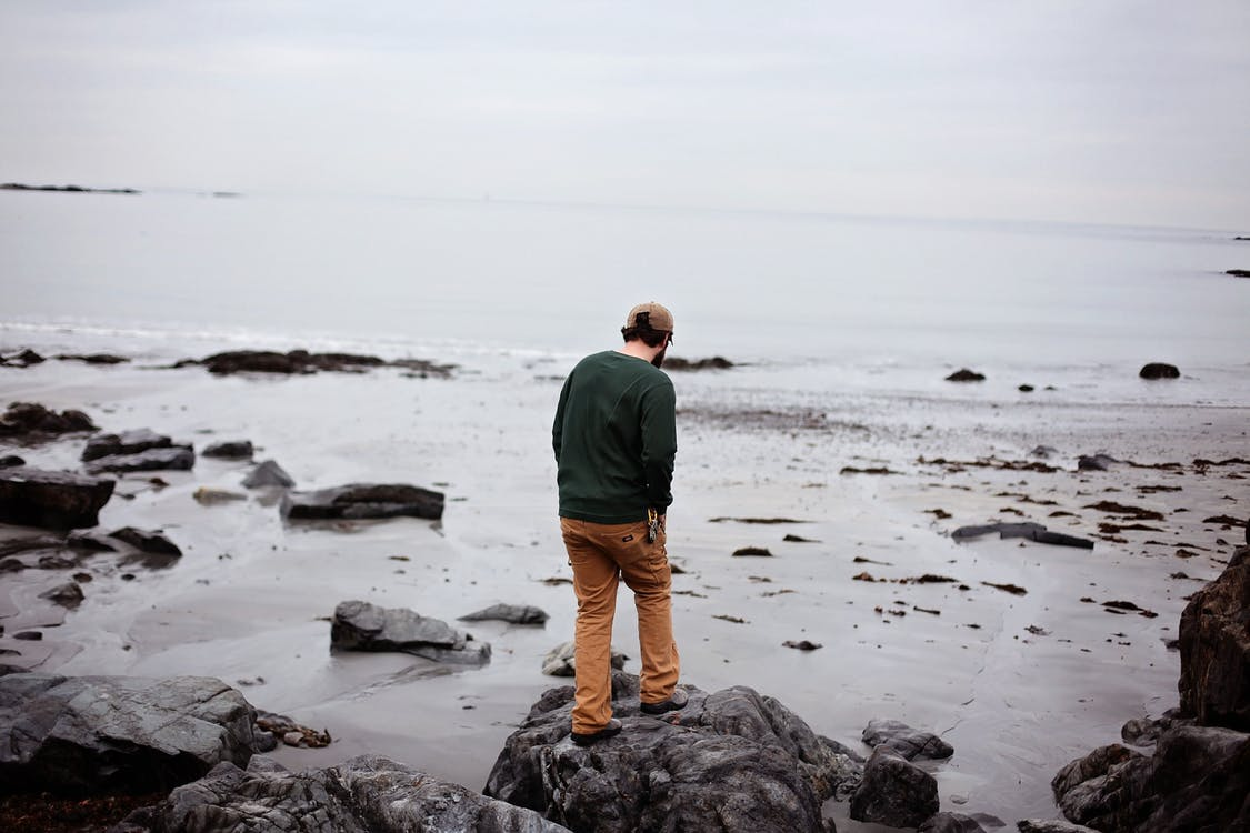 Man Standing on Rock Formation Near Body of Water