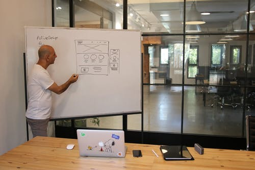 Focused male architect drawing scheme on whiteboard in office