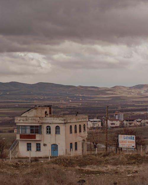 Grungy buildings on hilly terrain against overcast sky