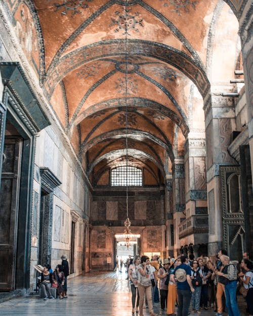 Anonymous tourists admiring interior of ancient church