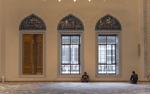 Anonymous men praying in mosque near windows