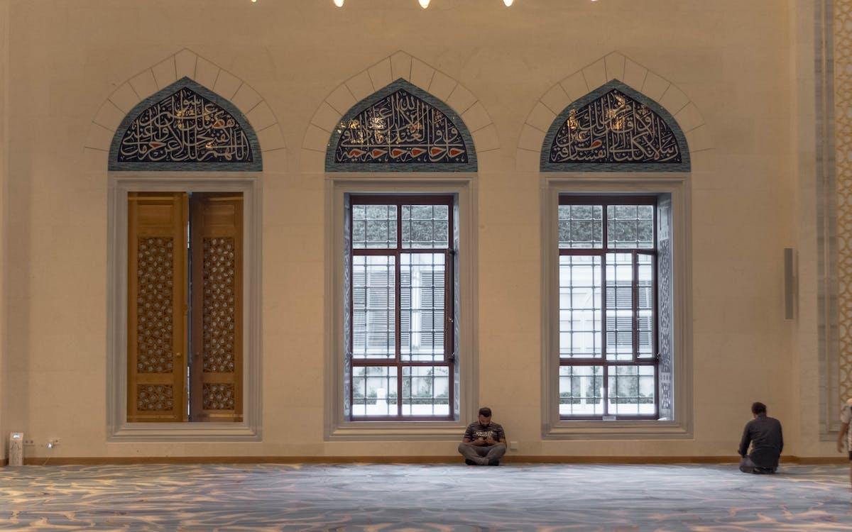 Anonymous men praying in mosque near windows