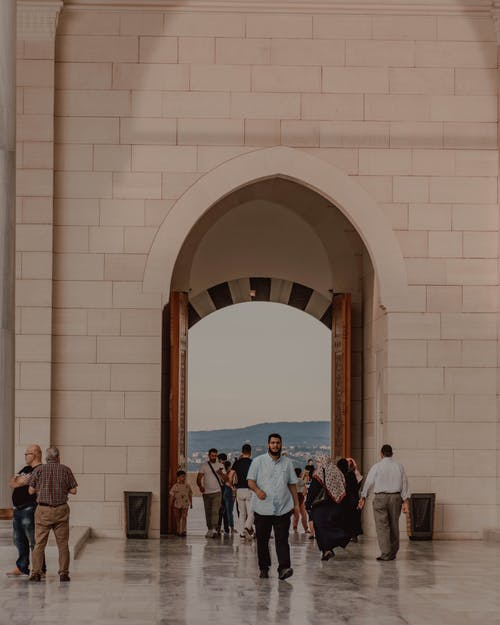 Tourists in casual clothes walking on cement floor near stone gates in Arabic decorations with picturesque view of cityscape in evening