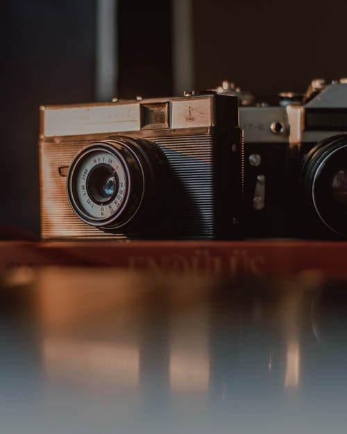Shabby vintage film photo cameras with retro old fashioned lens  and weathered body placed on wooden table with reflection