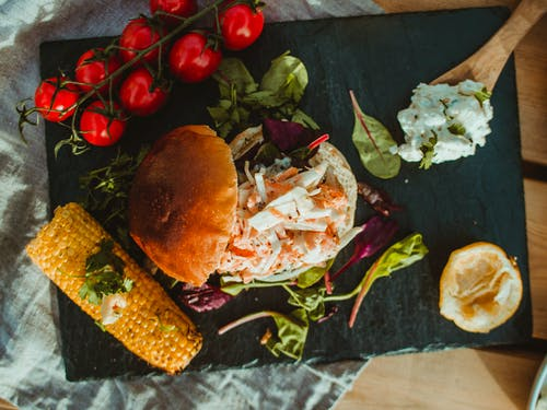 Tasty hamburger served with tomatoes and grilled corn