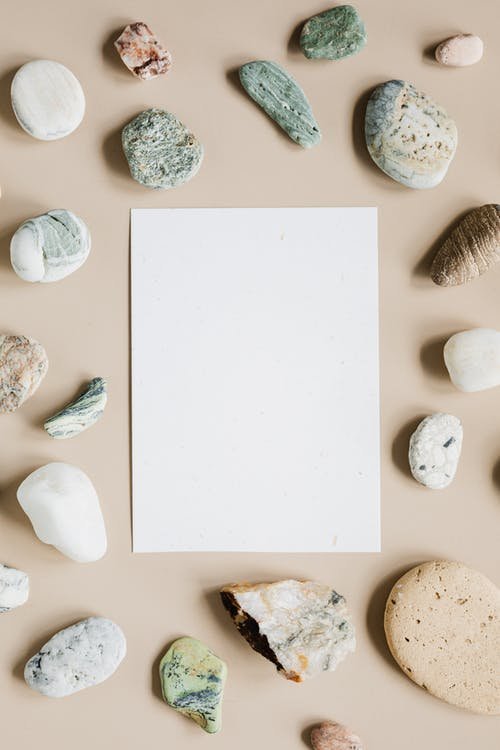 Top view composition of assorted whole and cracked pebbles arranged around white empty paper sheet on beige surface