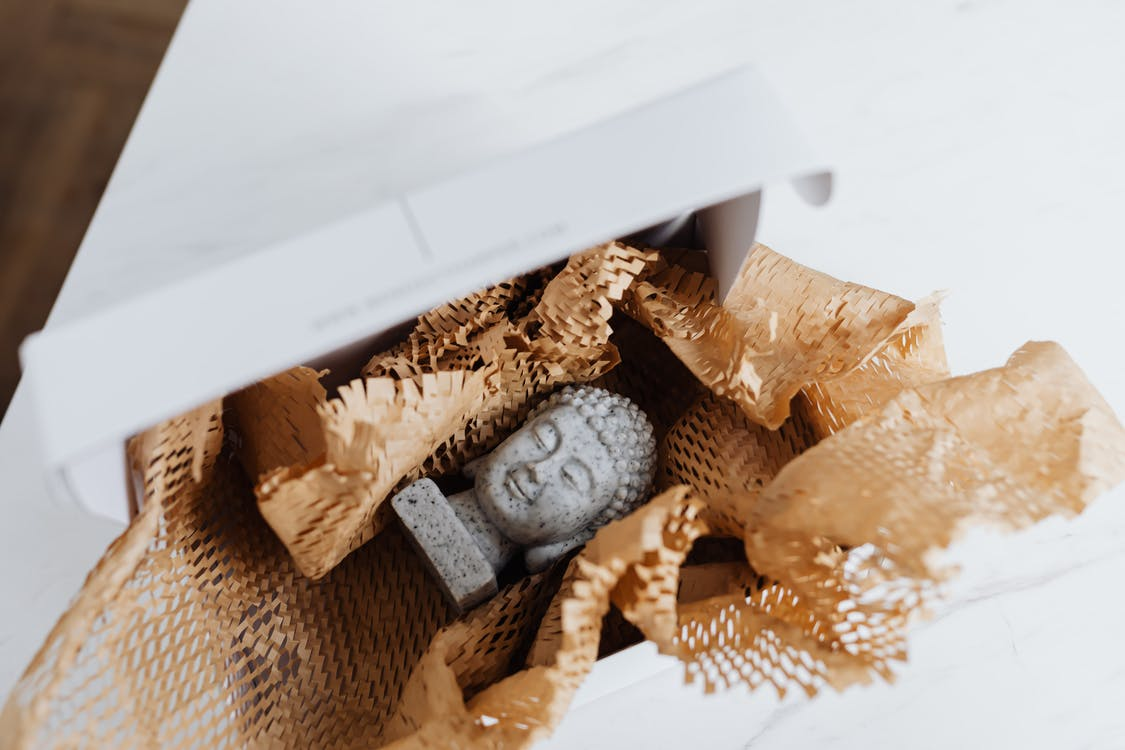 Granite Buddha bust in cardboard package