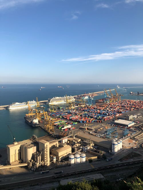 From above of modern loading harbor with cargo and infrastructure and seascape with ships floating on water in sunny day