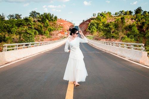 Stylish woman strolling along bridge