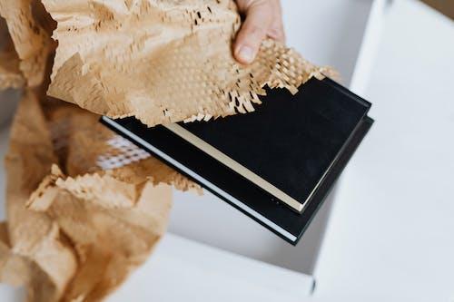 Crop man arranging packing paper on notebooks for sending