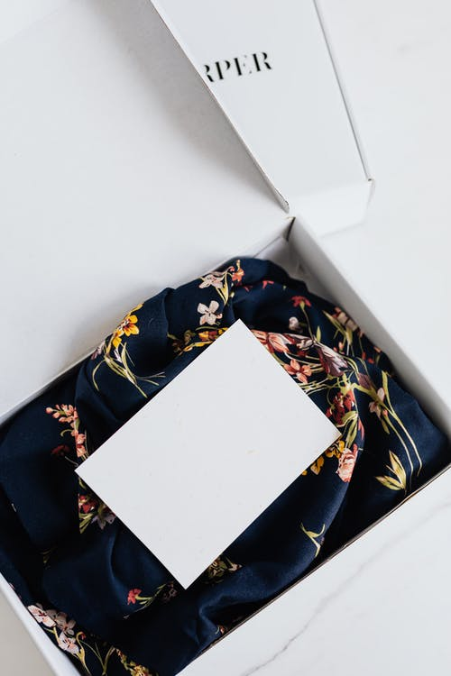 From above of stylish black silk floral pattern cloth with white visit card mockup placed in white carton box after receiving postal delivery of online order