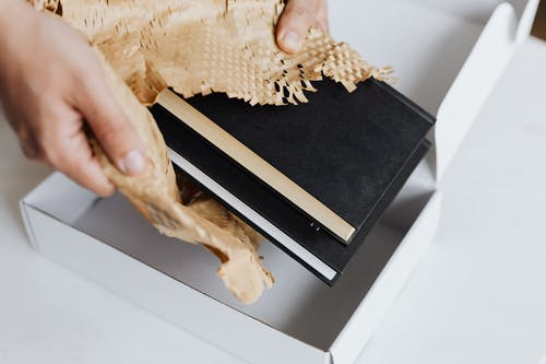 Anonymous man wrapping pair of black notebooks in packing paper