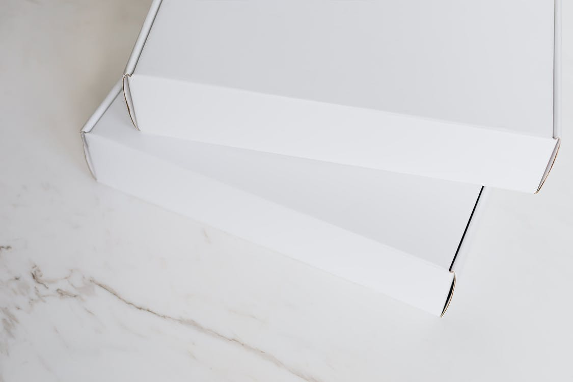 Set of white carton packages on marble surface