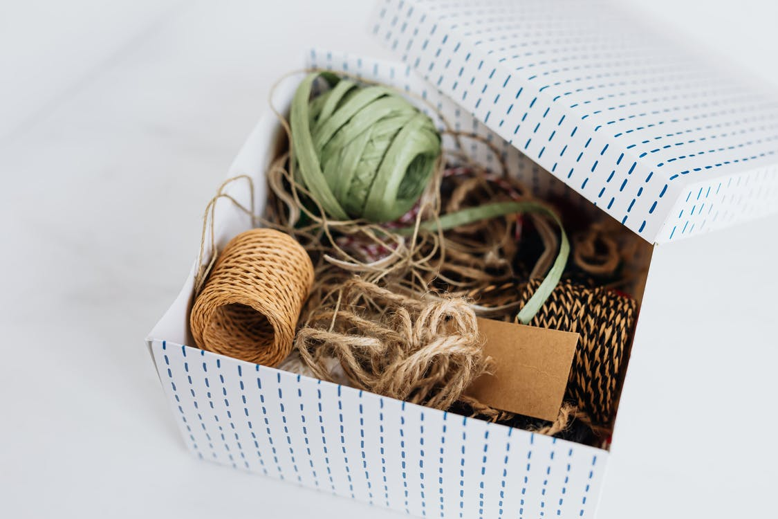 From above open carton box filled with various ribbons and ropes for holiday presents and gifts wrapping and blank brown cardboard card placed on white table