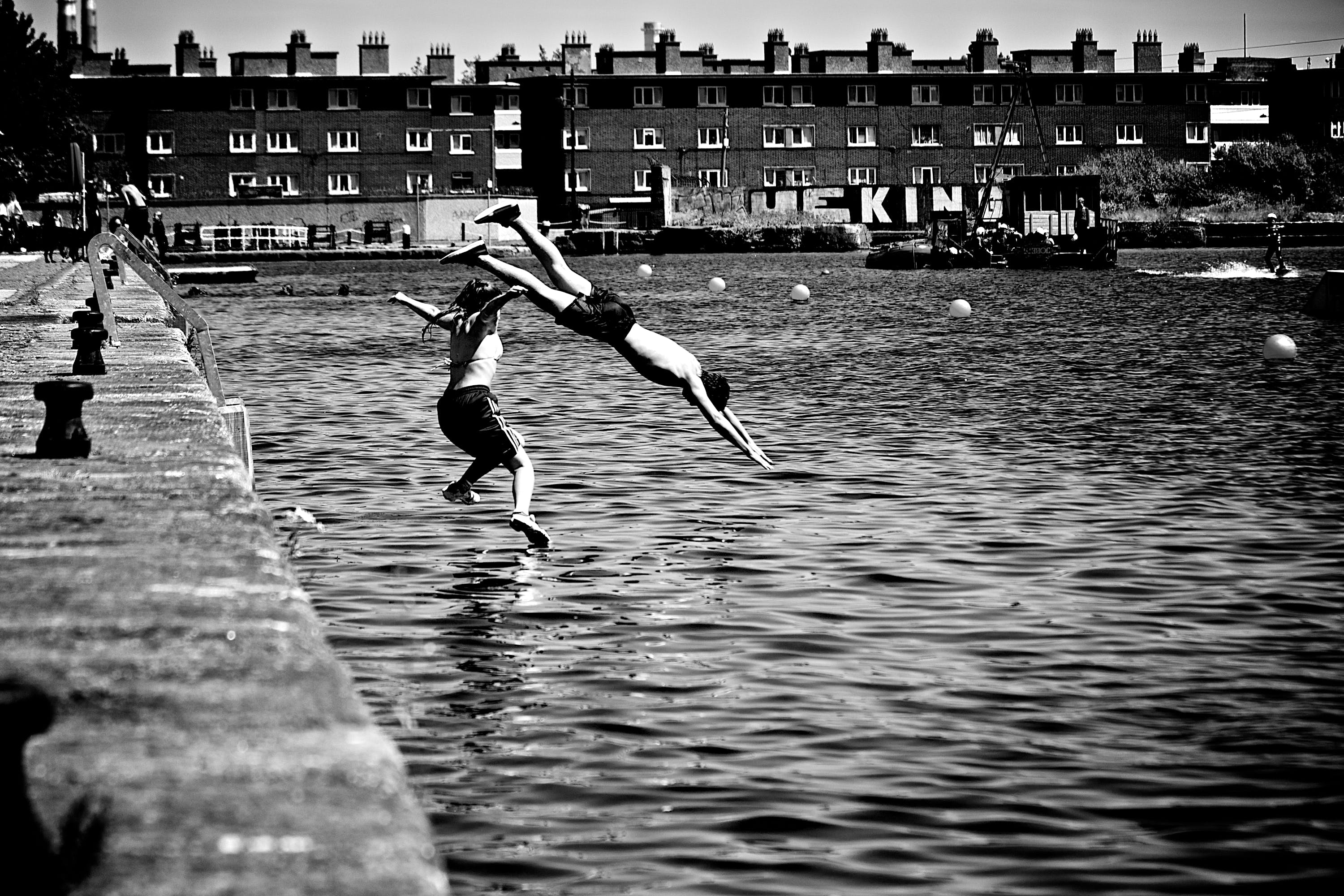 Boy and Girl Jumping in Body of Water