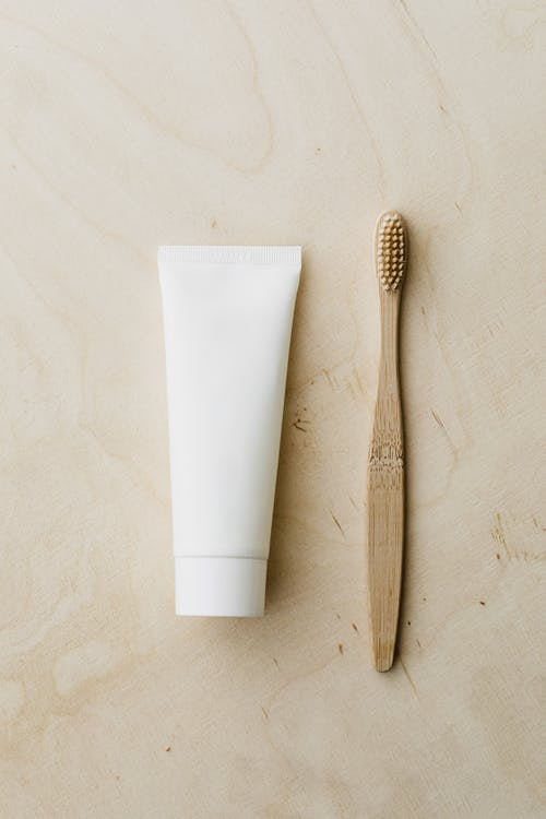 White toothpaste tube and bamboo toothbrush on wooden surface
