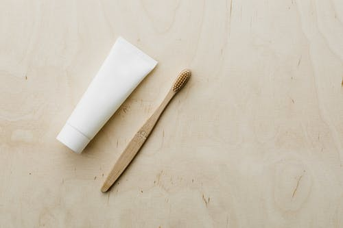 White tube and bamboo brush on wooden table
