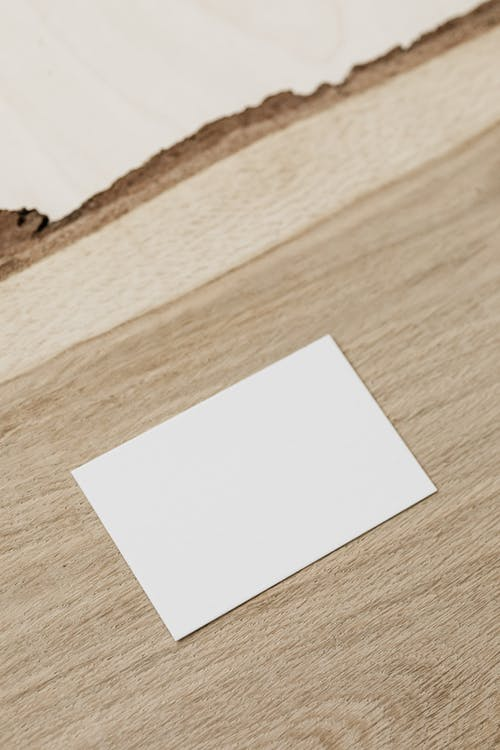 Empty white business card on wooden desk